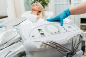 Cropped view of cosmetologist setting up machine for pressotherapy
