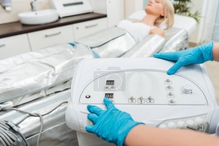 Photo for Cropped view of cosmetologist setting up machine for pressotherapy - Royalty Free Image