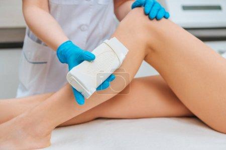 Photo pour Vue recadrée du cosmétologue dans des gants en caoutchouc appliquant de la cire sur la jambe - image libre de droit