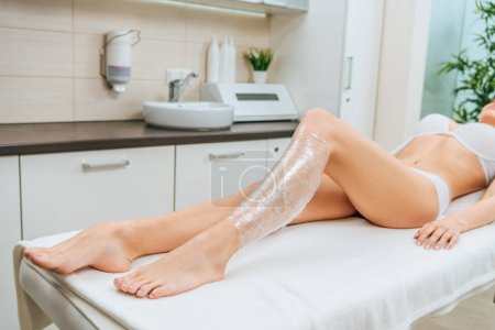 Cropped view of woman in underwear lying on beauty couch during body wrapping session