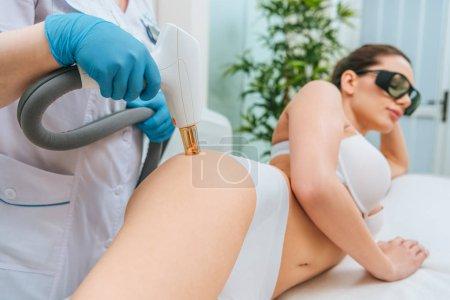 Photo pour Vue recadrée du cosmétologue dans des gants en caoutchouc faisant un traitement au laser - image libre de droit
