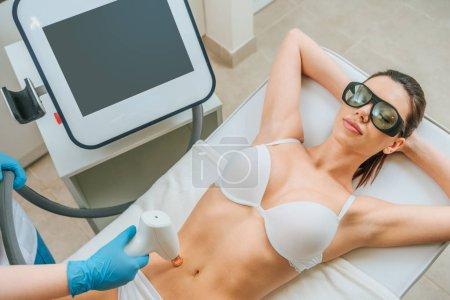 Relaxed woman in protective goggles receiving laser treatment in clinic