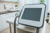 Laser machine with blank screen near beauty couch in clinic