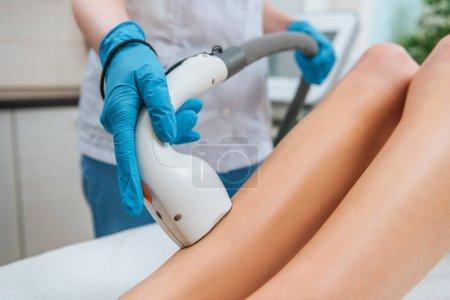Photo pour Vue partielle du cosmétologue dans des gants en caoutchouc faisant une procédure d'épilation au laser sur les jambes - image libre de droit