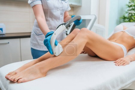 Photo for Partial view of cosmetologist in rubber gloves doing laser hair removal procedure on legs - Royalty Free Image