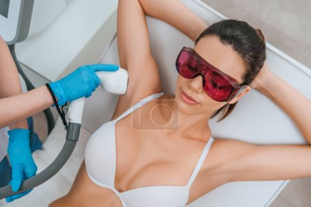 Photo for Woman in protective goggles receiving laser hair removal procedure on armpit - Royalty Free Image