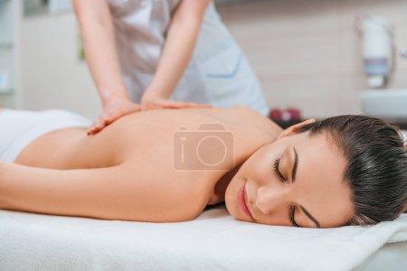 Photo pour Vue partielle du masseur fait massage du dos pour fille sur table de massage - image libre de droit