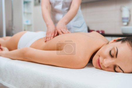 Photo for Partial view of masseur doing back massage to girl on massage table - Royalty Free Image