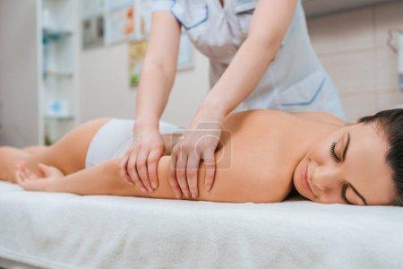 Photo pour Vue recadrée du masseur fait massage des bras pour fille sur table de massage - image libre de droit