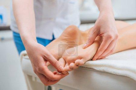 Photo pour Vue recadrée du masseur faisant massage des pieds à la femme sur la table de massage - image libre de droit
