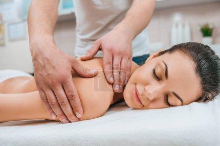 Photo pour Vue partielle du masseur fait massage du dos pour fille détendue sur table de massage - image libre de droit