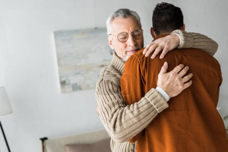 Photo for Senior man in glasses smiling while hugging son - Royalty Free Image