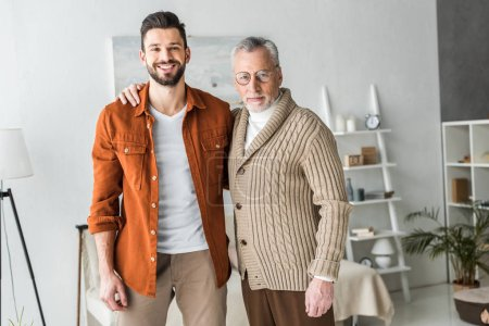 Photo for Handsome man smiling while standing with cheerful senior father - Royalty Free Image