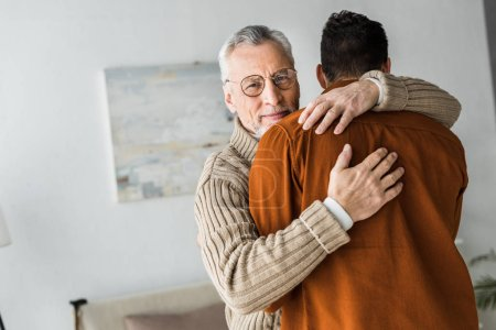 Photo for Happy senior man in glasses smiling while hugging son - Royalty Free Image