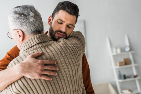 Photo for Handsome bearded man hugging elder father at home - Royalty Free Image