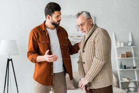 Photo for Handsome bearded man gesturing while looking at sad senior father - Royalty Free Image