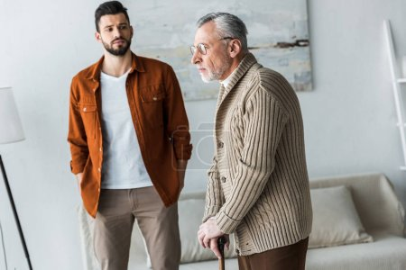 Photo for Handsome bearded son standing with hands in pockets and looking at sad senior father in glasses - Royalty Free Image