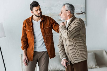 Photo for Handsome bearded son putting hand on shoulder of sad senior father in glasses - Royalty Free Image