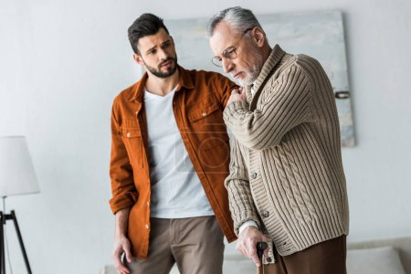 Photo for Handsome bearded son looking at upset senior father in glasses - Royalty Free Image