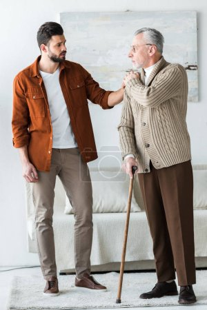 Photo for Handsome bearded son putting hand on shoulder of sad senior father in glasses with walking stick - Royalty Free Image
