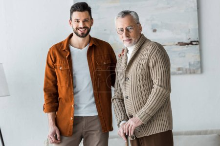 Photo for Handsome man smiling while standing with cheerful senior father in glasses - Royalty Free Image