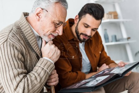 Photo for Handsome bearded man and senior father in glasses looking at photo album - Royalty Free Image