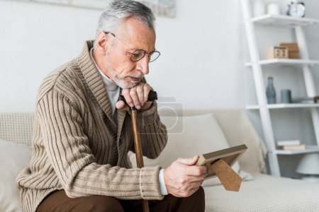 Photo for Upset retired man looking at photo frame while holding walking stick - Royalty Free Image