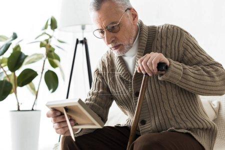 Photo pour Triste retraité cadre photo en regardant tout en tenant le bâton de marche - image libre de droit