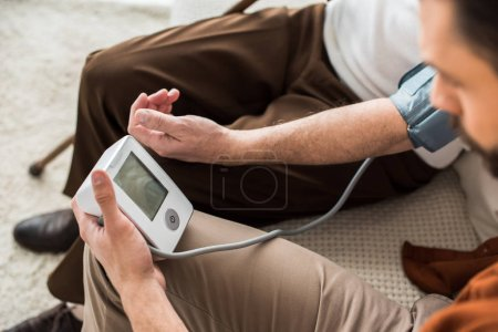 Photo for Man holding blood pressure meter while measuring blood pressure of senior father - Royalty Free Image