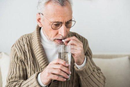 Photo pour Senior homme à lunettes prise de pilule à la maison - image libre de droit
