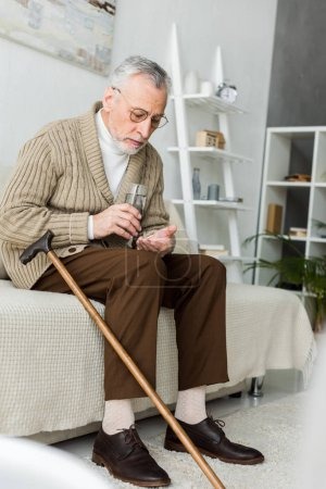 Photo for Senior man holding pill and glass of water while sitting on sofa near walking cane - Royalty Free Image
