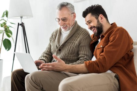 Photo for Cheerful bearded man gesturing while sitting with senior father and looking at laptop - Royalty Free Image