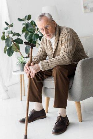 Photo pour Triste homme âgé dans des lunettes assis dans un fauteuil à la maison - image libre de droit