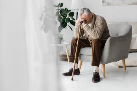 Photo pour Bouleversé retraité assis dans un fauteuil avec canne à pied à la maison - image libre de droit