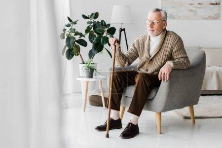 Photo pour Homme à la retraite dans des lunettes assis dans un fauteuil avec canne à pied - image libre de droit