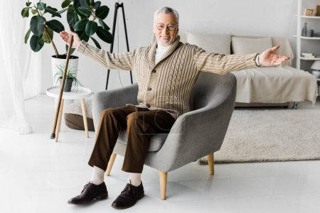 Photo pour Heureuse retraité dans des verres, assis dans le fauteuil avec la main tendue - image libre de droit