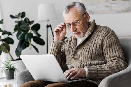 Senior mit Brille schaut zu Hause auf Laptop