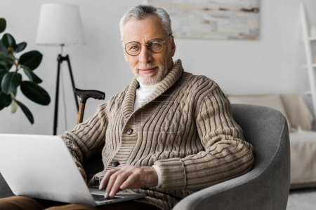 senior man in glasses looking at camera while sitting with laptop at home