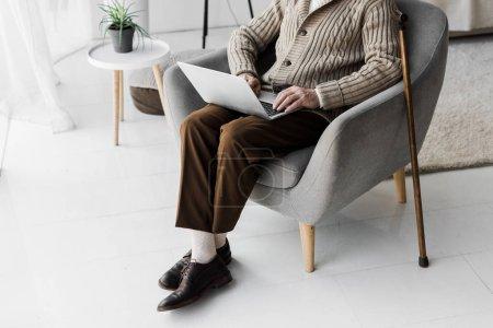 Photo pour Vue recadrée de l'homme âgé dans des lunettes en utilisant un ordinateur portable tout en étant assis avec les jambes croisées - image libre de droit