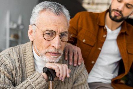 Photo pour Vue recadrée du fils barbu mettant la main sur l'épaule du père aîné triste dans des lunettes - image libre de droit