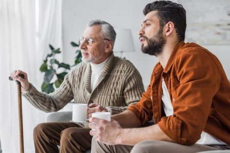 Photo for Retired father in glasses sitting with handsome man and holding cup - Royalty Free Image