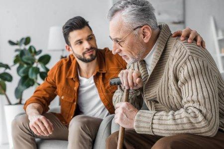 Photo pour Foyer sélectif de l'homme âgé et beau fils assis à la maison - image libre de droit