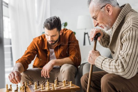 Photo for Selective focus of senior father in glasses playing chess with son - Royalty Free Image
