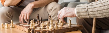 Photo for Panoramic shot of retired father and son playing chess at home - Royalty Free Image