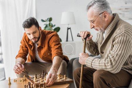 Foto de Padre superior en copas jugando al ajedrez con el hijo en casa - Imagen libre de derechos