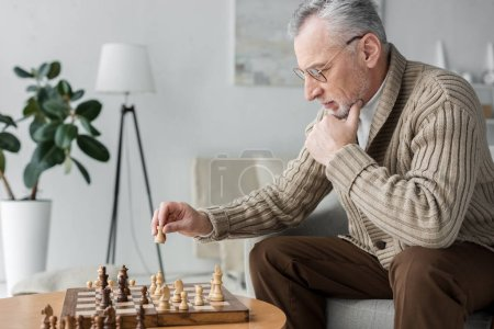 Photo for Retired man in glasses thinking while playing chess at home - Royalty Free Image
