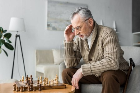 Photo for Pensive retired man in glasses thinking while playing chess at home - Royalty Free Image