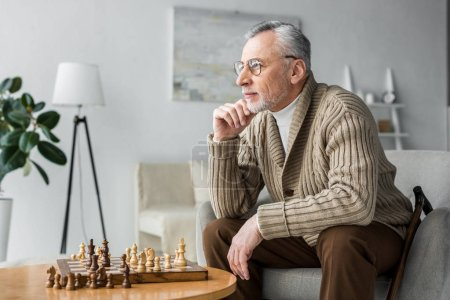 Photo for Thoughtful retired man in glasses thinking while sitting near chess board at home - Royalty Free Image