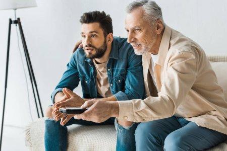 Foto de Mando a distancia Celebración alegre padre senior cerca guapo hijo mientras ve la tv en casa - Imagen libre de derechos