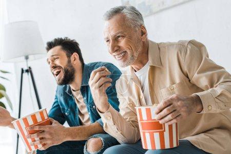Photo pour Heureux père aîné assis avec fils gai et tenant seau de maïs soufflé - image libre de droit